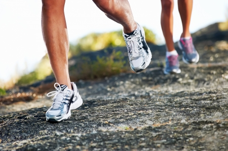 young woman running: trail running marathon fitness feet on rock fitness and healthy lifestyle