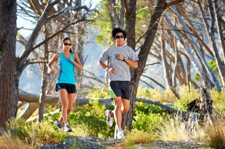 couple running on trail in woods having fun athletes