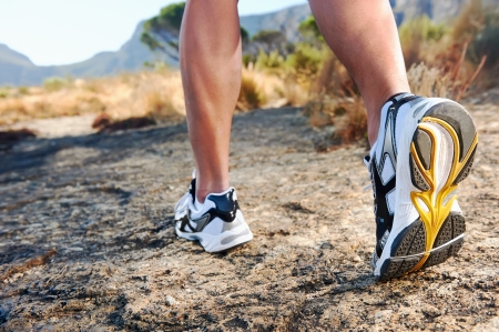 person walking: trail running athlete feet on rock excercising fitness and healthy lifestyle Stock Photo