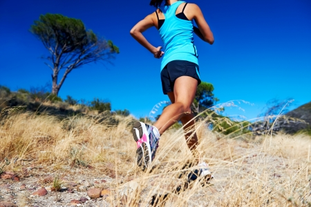 trail running: woman running on nature trail sunny day blue sky and jumping athlete
