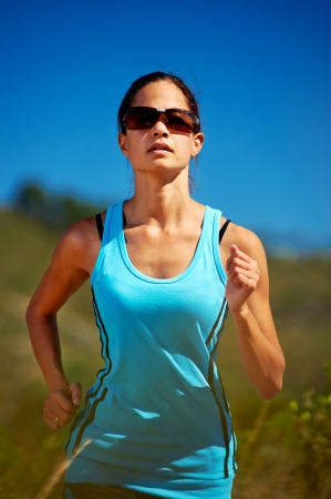 portrait of runner athlete on sunny day with blue sky photo