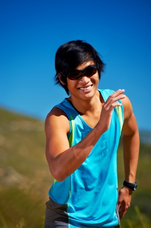 Healthy happy asian man running outdoors in summer smiling photo