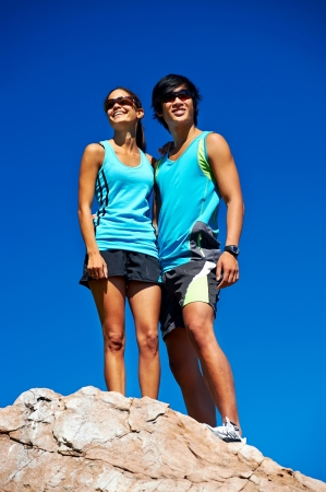 couple trail running on mountain at top celebrating with confident smile and healthy lifestyle photo