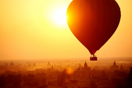 hot: Silhouette of hot air balloon over Bagan in Myanmar, tourists watching sunrise over ancient city Stock Photo