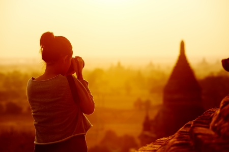 myanmar: female traveller photographing temples at Bagan Myanmar Asia at sunrise