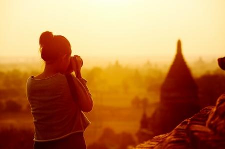 utazási: női utas fényképezés templomok Bagan Myanmar ázsiai napkeltekor