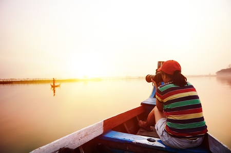myanmar: Female backpacker on vacation taking photo of local fisherman on boat in asia sunset