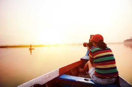 personas tomando agua: Mujer mochilero de vacaciones tomando la foto de los pescadores locales en el barco en la puesta del sol asia