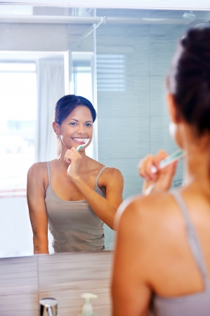 Portrait of attractive woman brushing teeth in bathroom and looking in the mirror at reflection. healthy teeth. Stock Photo - 18937949