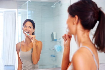 Portrait of attractive woman brushing teeth in bathroom and looking in the mirror at reflection. healthy teeth. Stock Photo - 18937931