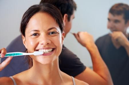 daily routine: despreocupada pareja de verdad cepillarse los dientes en el ba�o juntos. la salud dental de rutina diaria