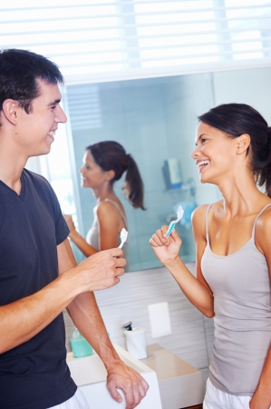 carefree real couple brushing teeth in the bathroom together. daily routine dental health photo