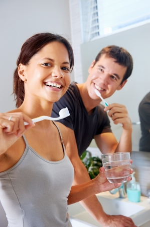 bathroom mirror: carefree real couple brushing teeth in the bathroom together. daily routine dental health