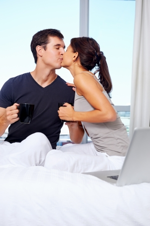young couple enjoy coffee and relax at home with laptop and love photo