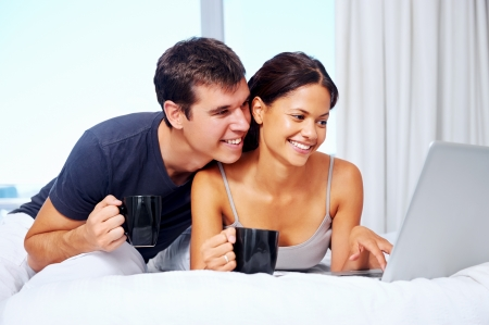 young couple enjoy coffee and relax at home with laptop and love Stock Photo - 18937939