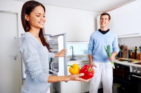 pareja comiendo: pareja sana de comer obtener verduras frescas de la nevera para cocinar los alimentos