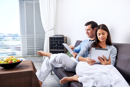 couple relaxing at home with tablet computers reading in the living room on the sofa couch. Stock Photo - 18937944