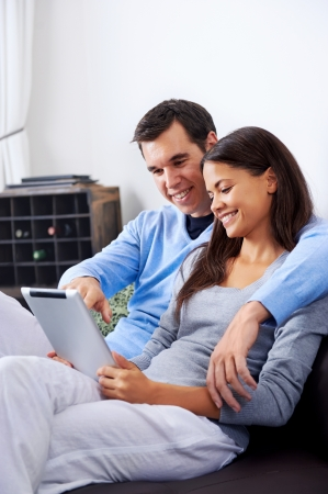 couple relaxing at home with tablet computers reading in the living room on the sofa couch. Stock Photo - 18937907