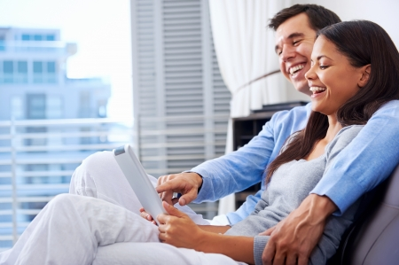 couple relaxing at home with tablet computers reading in the living room on the sofa couch. Stock Photo - 18937937