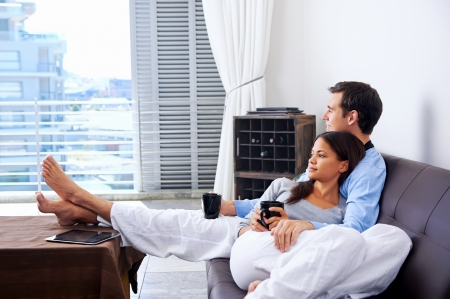 home comfort: Couple relax at home with cup of coffee and sofa couch. happy healthy relationship