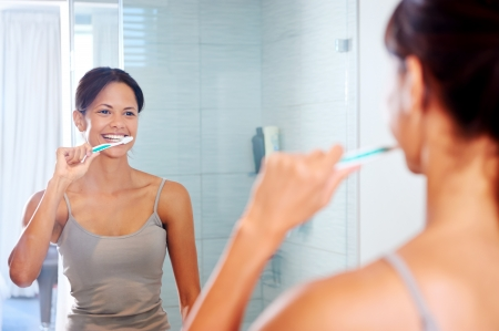 bathroom mirror: Portrait of attractive woman brushing teeth in bathroom and looking in the mirror at reflection. healthy teeth. Stock Photo
