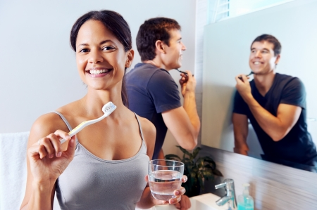 Bathroom routine for happy young couple brushing teeth and shaving in mirror Stock Photo - 19124565