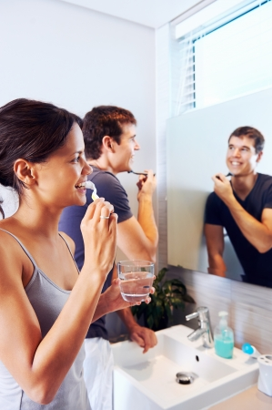 Bathroom routine for happy young couple brushing teeth and shaving in mirror Stock Photo - 19124563
