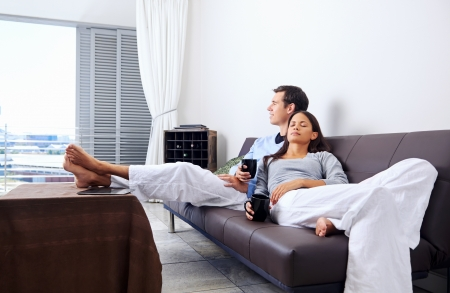 woman relaxing: Couple relax at home with cup of coffee and sofa couch. happy healthy relationship