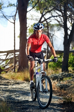 bicyclists: Mountain bike cyclist athlete in forest riding on rocks Stock Photo