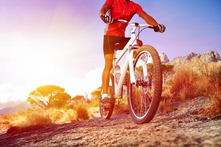 ciclismo: �ngulo de visi�n baja de ciclista en bicicleta de monta�a en el sendero rocoso al amanecer