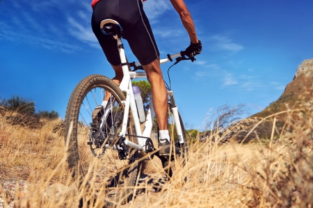 bike race: mountain bike man with blue sky riding on outdoor trail in nature