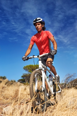 mountain biker: mountain bike man with blue sky riding on outdoor trail in nature