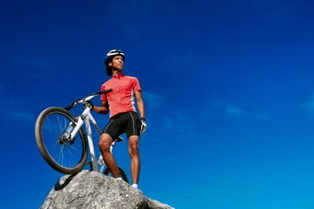 confident mountain bike man celebrating making the top of the peak happy and cheerful photo