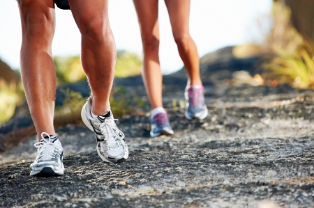 woman running: trail running marathon fitness feet on rock fitness and healthy lifestyle