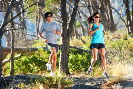 girl jogging: couple running on trail in woods having fun athletes