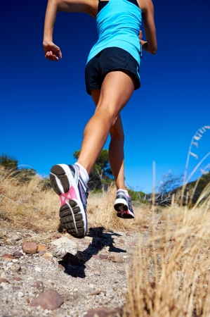marathon running: woman running on nature trail sunny day blue sky and jumping athlete