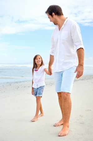 dad daughter: Father and daughter holding hands on the beach together happy and loving vacation