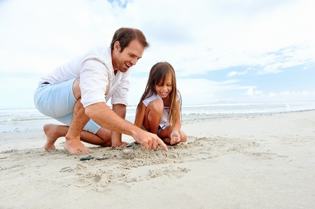 Father and daughter day at the beach collecting shells together having fun and smiling Stock Photo