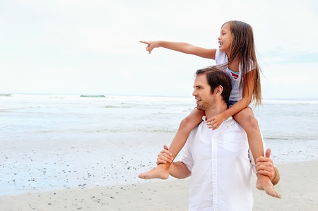 father daughter: daughter on dad shoulders pointing while at the beach Stock Photo