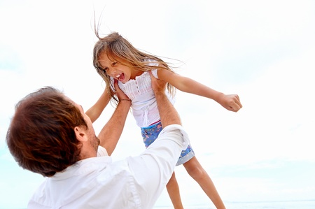 toss: Healthy father and daughter playing together at the beach carefree happy fun smiling lifestyle
