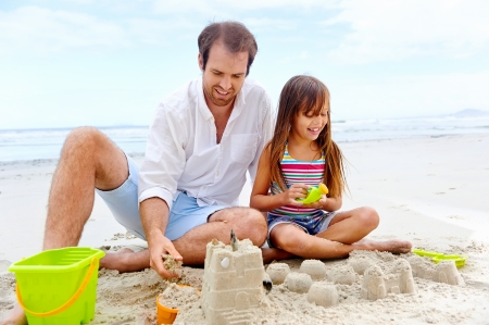 children sandcastle: happy healthy family father and daughter building sand castle on the beach smiling and carefree Stock Photo