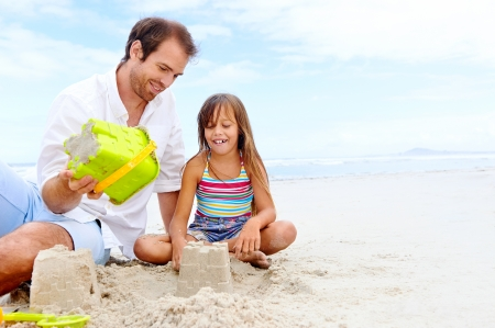 happy healthy family father and daughter building sand castle on the beach smiling and carefree photo