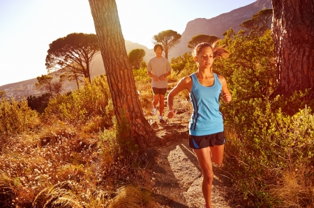 Trail running marathon athlete outdoors sunrise couple training for fitness and healthy lifestyle photo