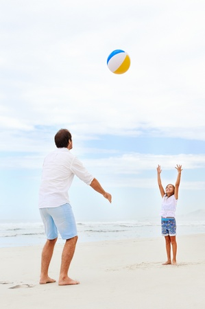 beach ball girl: Father and daughter playing on the beach together having fun with beachball