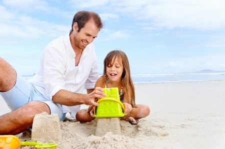sandcastle: happy healthy family father and daughter building sand castle on the beach smiling and carefree Stock Photo