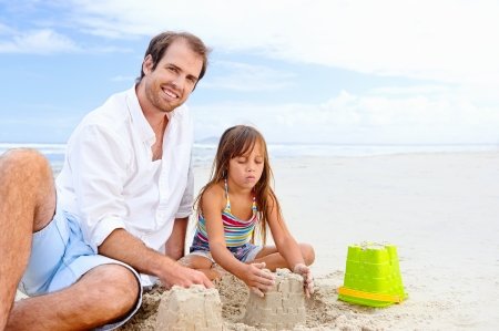 playing in the sea: happy healthy family father and daughter building sand castle on the beach smiling and carefree Stock Photo