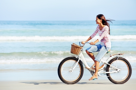 bicycle: carefree woman with bicycle riding on beach sand having fun and smiling