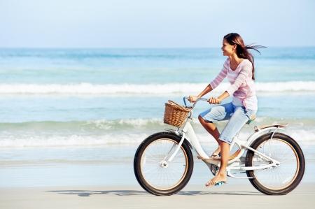 andando en bicicleta: Mujer despreocupada con la bicicleta a caballo por la playa de arena que se divierte y sonriente