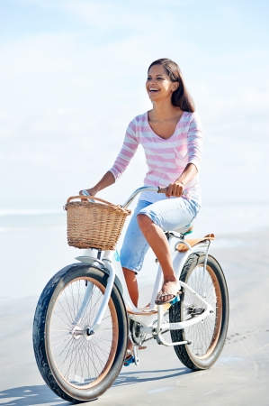 carefree woman with bicycle riding on beach sand having fun and smiling photo