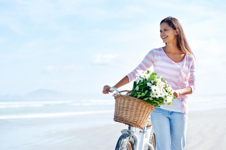 bicycle girl: woman with bicycle and flowers in basket smiling carefree and happy